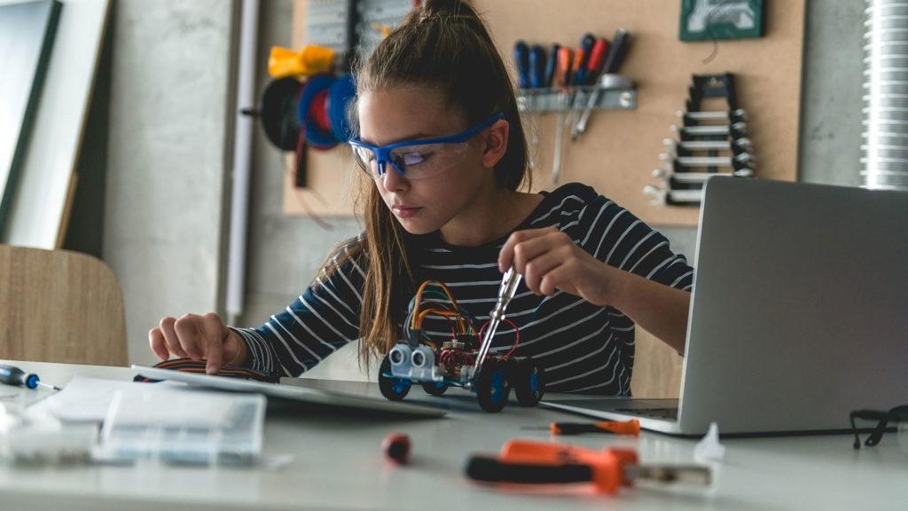 Stem Education girl working on robot at home workshop